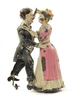 A Bavarian Painted Tin Toy, Gunthermann, Tango Dancers, depicting a couple dancing the tango with allover polychrome paint decoration. Height 7 3/4 inches.