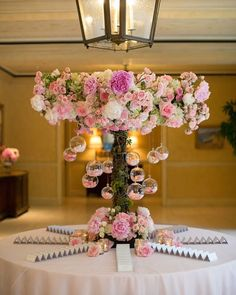 Round escort card table decorated with an arrangement of roses and peonies in pink and white, moss, and suspended glass orbs filled with petals ~ https://www.insideweddings.com/weddings/pink-white-wedding-with-ombre-details-at-montage-laguna-beach/686/