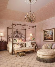 Romance is the mood in this bedroom suite, with its curvy iron canopy bed, hand stenciled wall treatment, and chaise lounge. The chandelier is made of multi-colored glass. Linda Shears Designs, Ltd | Michigan Design Center