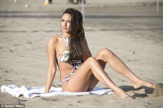 Sitting pretty: The model swept her long dark locks to the side and highlighted her pretty...
