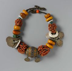 Necklace 19th century DIMENSIONS Overall: 4.4 x 4.4 x 57.2 cm (1 3/4 x 1 3/4 x 22 1/2 in.) ACCESSION NUMBER 2006.5 MEDIUM OR TECHNIQUE Amber, coral, glass, enameled metal, coins, and other media; on cord | Museum of Fine Arts, Boston