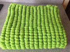 Rico pompon Marshmallow blanket in lime green.