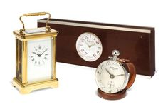 A GILT-BRASS CARRIAGE TIMEPIECE CLOCK ASPREY, LONDON, LATE 20TH CENTURY The glass to top of case etched with Prince of Wales feathers, in gilt-tooled leather presentation case also with Prince of Wales feathers to top; together with a ball clock on leather stand by Hermes and a brushed stainless steel mounted mahogany desk clock by Asprey