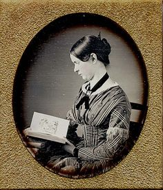 1850's image showing a woman looking at Godey's Ladies Book