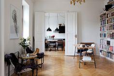 In het mooie Malmö. Dit complex werd gebouwd in begin jaren 1900 en alle elementen zoals het hoge plafond, de klassieke deurkozijnen zijn netjes behouden. Dat maakt deze woning een echt pareltje om te zien. De visgraatvloer en de gracieuze dubbele witte deuren geven de inrichting een klassieke uitstraling, terwijl de speelse inrichting met verschillende vormen en strakke zwarte keuken dit weer doorbreken. Casual, klassiek en modern