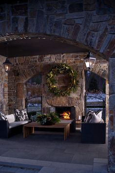 An oversized wreath complements the large scale of this outdoor living room - Traditional Home® / Photo: John Bessler / Design: Lucy Earl