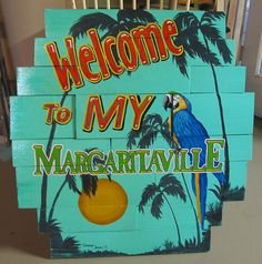 Margaritaville sign made from a old table top with fresh boards screwed on top, huge sign, parrots and palms.