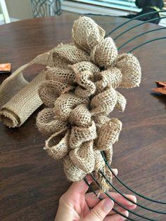 coronas de navidad, tutorial para hacer corona navideña de arpillera con base de metal, mesa de madera, mano mujer