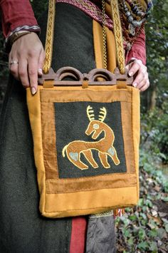 Viking bag with Birka inspired emboidery and tablet weaving. Made in wool, silk and linen. The Hedeby woods are  made of Oak and carved by Wyrm Crafts.