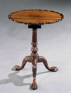 *A GEORGE III TRIPOD PIECRUST TABLE: The table has a beautifully faded piecrust top supported on a 'bird-cage' above a fluted column and with leaf carved vase. Below, the legs each with carved bell flowers and scrolling acanthus leaves with unusual 'pipped' decoration and terminating in claw and ball feet. English, Circa 1765