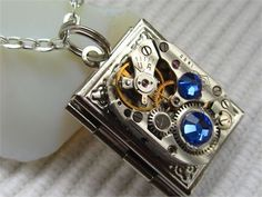 Steampunk silver plated locket necklace with Royal blue Swarovski crystals. Vintage watch movement is 3/4 long and the locket is 7/8 long and 3/4 wide. It hangs from 24 of silver plated steel chain, there is a lobster claw clasp at the back . The locket opens out to reveal two sections for photos. I have the same locket with green Swarovski crystals. Comes in a gift bag. I have book lockets with other Swarovski colours and with no stones. How to put a picture in the locket http...