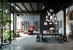 Popular opinion holds that dark living spaces are an interior design no-no, but this industrial Milan loft proves that rules were made to be broken.