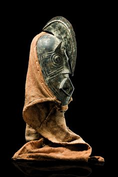 "Burkina Faso, Bwa bronze, dark, partly encrusted patina, of oval form, circular protruding eyes surmounted by small, pointed ears, a rhomb-shaped mouth with visible teeth underneath, the facial plane bisected by an elongated, sickle-shaped forehead crest, a bonnet made from rough cloth on the back, min, dam., slight traces of abrasion, on metal base; these masks represent the spirit ""hombo"", a protective spirit of the blacksmith. Most of the masks depict beings from the bush"