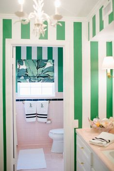 kelly green cabana striped walls pair perfectly with palm inspired window coverings and the oh-so 50's pink tile.
