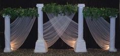 Idea for backdrop of head table - columns and tulle with some lights?  Could use some sheer curtains/drapes instead of tulle?