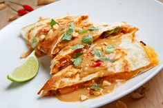 """Spicy Peanut Chicken Quesadilla...  10"""" Tortilla, 1/4 cup shredded Jack, 1/4 cup shredded Cheddar, 1/4 cup warm, cooked, shredded Chicken, 2 Tbsp Spicy Peanut Sauce, 1 sliced Green Onion, 1 Tbsp torn Cilantro... Place tortilla in pan. Sprinkle half cheese over half tortilla. Top with chicken, sauce, green onion, cilantro & remaining cheese. Fold in half. Cook 2-4 min on each side til golden brown & cheese is melted. Serve garnished with sauce, chopped peanuts, green onions & cilantro."""