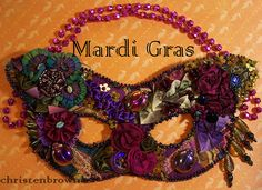 I ❤ ribbonwork and beadwork. . . Mardi Gras Mask- The mask is made from scraps of fabric, ribbon, and thread lace. I have added in ribbon worked flowers and leaves; vintage glass buttons; glass bead embellishments; and vintage and new sequins to create this festive mask.  (My daughter provided the beads for the hanger!)