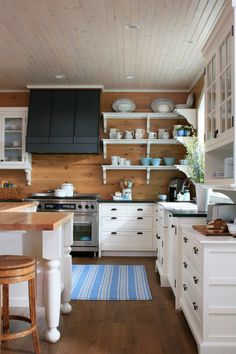 planked wood walls with white cabinets - country kitchen