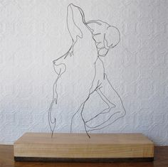 Gavin Worth #fineart #wire #sculpture  In this unconventional piece, Worth shaped the upper torso of a woman's body with the use of black wire, on the base of a block of wood. I was very drawn to this work because the wires were able to show the detail in the body's form and value.