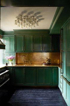 Выкрашенные в изумрудный цвет фасады кухни прекрасно сочетаются со столешницей и фартуком из латуни и полом из черного дерева.