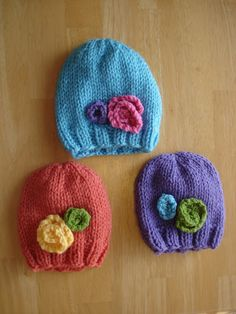 Free Knitting Pattern! Baby In Bloom Hats. Preemie, Newborn and Toddler sizes. Knit flat or in the round. Would also be cute with pom-poms instead of flowers.
