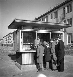 Kioski w Warszawie z lat 50 stanowiły nieodłączny element miejskiej przestrzeni. Najzgrabniejsze były kioski Ruchu, takie właśnie jak ten oglądany na fotografii Zbyszka Siemaszki. Przeszklone pojawiły się dopiero w latach 60. Te z lat pięćdziesiątych były drewniane.