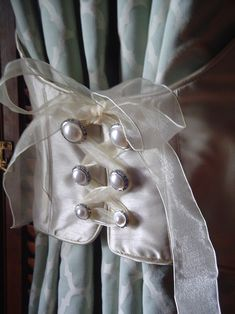 Corset style Curtain tie-back: Laced up with a silk ribbon around pearl buttons. Aaaww!! I love this!!!!! Must have for my bedroom!