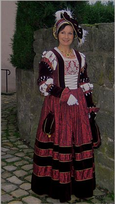 Nobility cranach dress made of silk damask in pomegranate and velvet , brustflect of beadwork (in the background remains of the wall of Horn castle in North-West Germany)