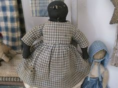 19th Century Black RAG DOLL from James Cramer Collection Seven Gates Farm. Early Black Rag Doll is dressed in her Original  Early Homespun Clothing with a Blue and White Homespun dress that has taken on more of a Gray color on the outside of the homespun that happens with age.    She has her Early Under Shirt, Early Pantaloons, and Early under Skirt. (ebay)