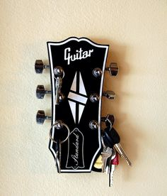 Hello guitar lovers!!!! Turn some heads with this amazing looking key holder. Designed in the style of a Gibson Les Paul, one of the most iconic and easily recognized guitars ever made!!! The face of the rack is made from two tone acrylic with a wood back and comes with actual chrome guitar tuning pegs that just adds a fantastic look of realism to a unique key holder. Can be ordered either in the two tone black and white or all black. Guitar gunslingers, metal maniacs and axe wielding…