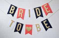 This Bride To Be banner is made with navy blue, white and coral background flags, each flag is adorned with a gold glitter letter and everything is