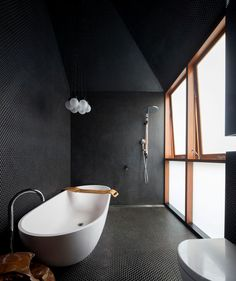 Small black penny tiles cover the surfaces in this modern black bathroom, and a frosted windows provides natural light, while a white freestanding bathtub keeps things bright. #BlackBathroom #ModernBathroom #BathroomDesign