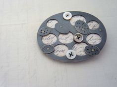 Layered ovals brooch | oxidised silver, old postcard, gold, perspex, old mother-of-pearl buttons | by Clare Hillerby