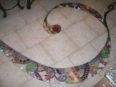 Lay out the tile & number them bf hand. Draw out swirl. Cut w/ diamond bit. Install. Then fill in w/ mosaic.