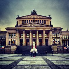 Historic square bounded by twin churches, a chocolate shop, and the Berlin Symphony's concert hall.