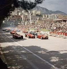 View of racecars at the start of the Grand Prix de Monaco in Monte Carlo, Monaco, May 13, 1956. British driver Stirling Moss (later Sir Stirling Moss) (#28, center), in a Maserati 250F, went on to win the race. Others visible include Argentinian Juan Fangio (#20) and Italian Eugenio Castellotti (#22), both in Ferraris on either side of Moss.