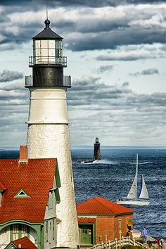 Two Lighthouses In The Same. In this photo you can see both the Portland Head Lighthouse and the lessor known Ram Island Ledge Light. A sail boat passes in between enjoying the view.