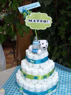 MATEO's diaper cake Baby shower  Diaper cake  Blue and green  Stuffed animal at the top  Three tier disposable diaper cake   MATERIALS:  Rubber bands Plastic bottle straight shape  Masking tape  Ribbon  Stuffed animal  Bows  Disposable small diapers  Plastic baby bottle   WHAT TO DO:  1. Roll diapers and secure with rubber band right in the middle  2. Start at the bottom and place diapers all around the plastic bottle,  make three layers.  Secure with rubber band  3. Add two more layers to…