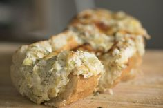 Stuffed Artichoke Bread INGREDIENTS  1/2 cup non-marinated artichoke hearts, drained and chopped 1 loaf crusty bread 1/4 cup sour cream 1/4 cup mayonnaise 1/2 cup (softened) cream cheese, room temperature 1 cup grated parmesan cheese, divided 1 clove garlic, minced 1/2 teaspoon fresh dill Salt and pepper to taste