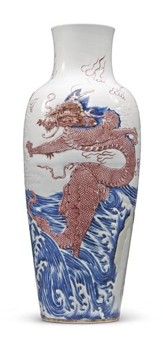 RARE UNDERGLAZE-BLUE AND COPPER-RED 'DRAGON' VASE, QING DYNASTY, KANGXI PERIOD, the rounded shoulders gently tapering towards the base, the sides carved in low relief with two dragons rising from turbulent seas, the details of the decoration highlighted in underglaze-blue and copper red, H 16 3/4 in.