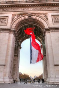 the French flag hanging from the Arc de Triomphe