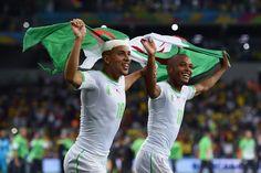 Sofiane Feghouli et Yacine Brahimi courent sur la pelouse du stade de Curitiba, drapeau algérien en l'air.