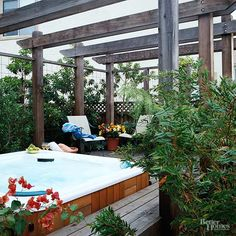 Seclusion in this spa is ensured with an overhead pergola, wire-mesh screening, and lush foliage.