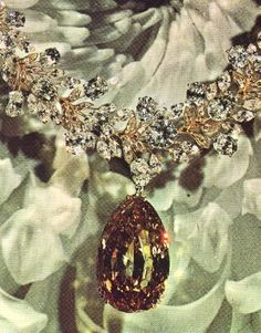 In the summer of 1963, a 198.28-carat fancy brown diamond was found in the South African diamond fields. This unusual stone was purchased by Julius Cohen, New York City manufacturing jeweler, under whose direction it was fashioned by the firm of S & M Kaufman into a Fancy Orange-Brown 104.16-carat pear shape. The stone has a total of 189 facets (67 on the crown, 65 vertical facetrs along the girdle, and 57 on the pavilion) and measures 24.98 mm wide, 39.10 mm long, and 16.00 mm deep. It has…