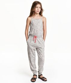 Jumpsuit in soft, melange jersey. Narrow shoulder straps, elasticized seam and drawstring at waist, side pockets, and tapered legs with ribbed hems.