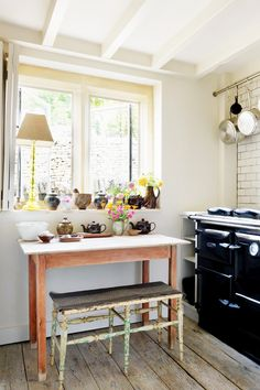 Small bench in kitchen with wood table and floral arrangement