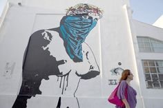 """#thalo In this photo made on Wednesday, June 17, 2015 a woman walks past a graffiti artwork titled """"Athena vs Europa, Resist vs Submit"""" by French street artist Goin at the Athens School of Fine Arts -"""