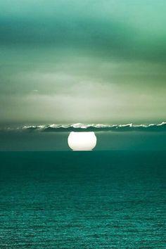 Moon on turquoise sea.