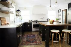 black kitchen, island with butcher block, white counters, backsplash, and rangehood, wood accents, floating shelves, glass globe penants, wood pocket door.The Full Kitchen Reveal | Chris Loves Julia
