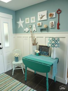 An entryway gallery wall with a cottage, ocean theme in turquoise, cream and red